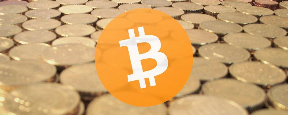 O imagine cu monede cu logo-ul Bitcoin peste ele
